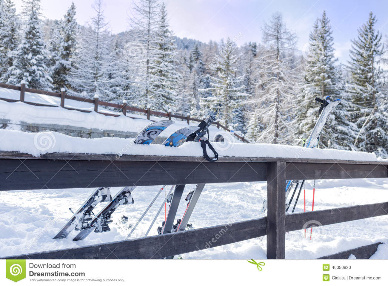 Skis and ski poles leaning against a fence stock photo