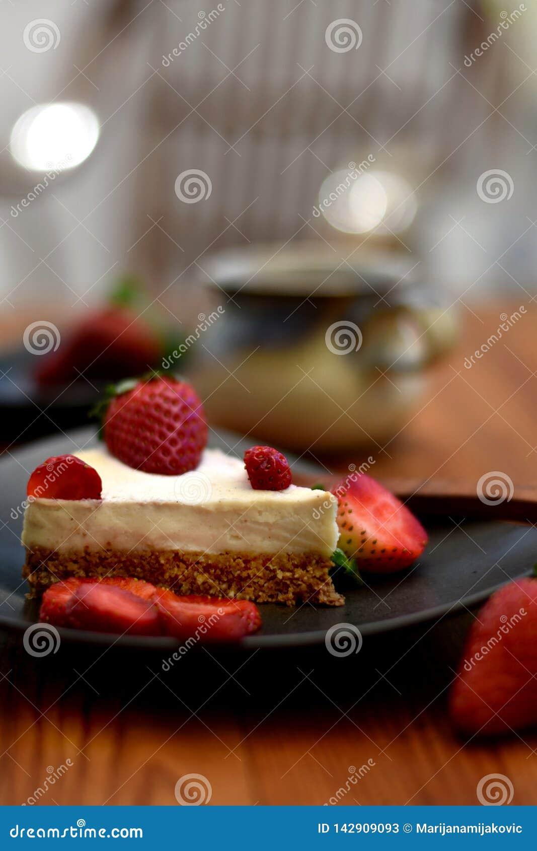 Skiva av den rå jordgubbekakan på en brun platta