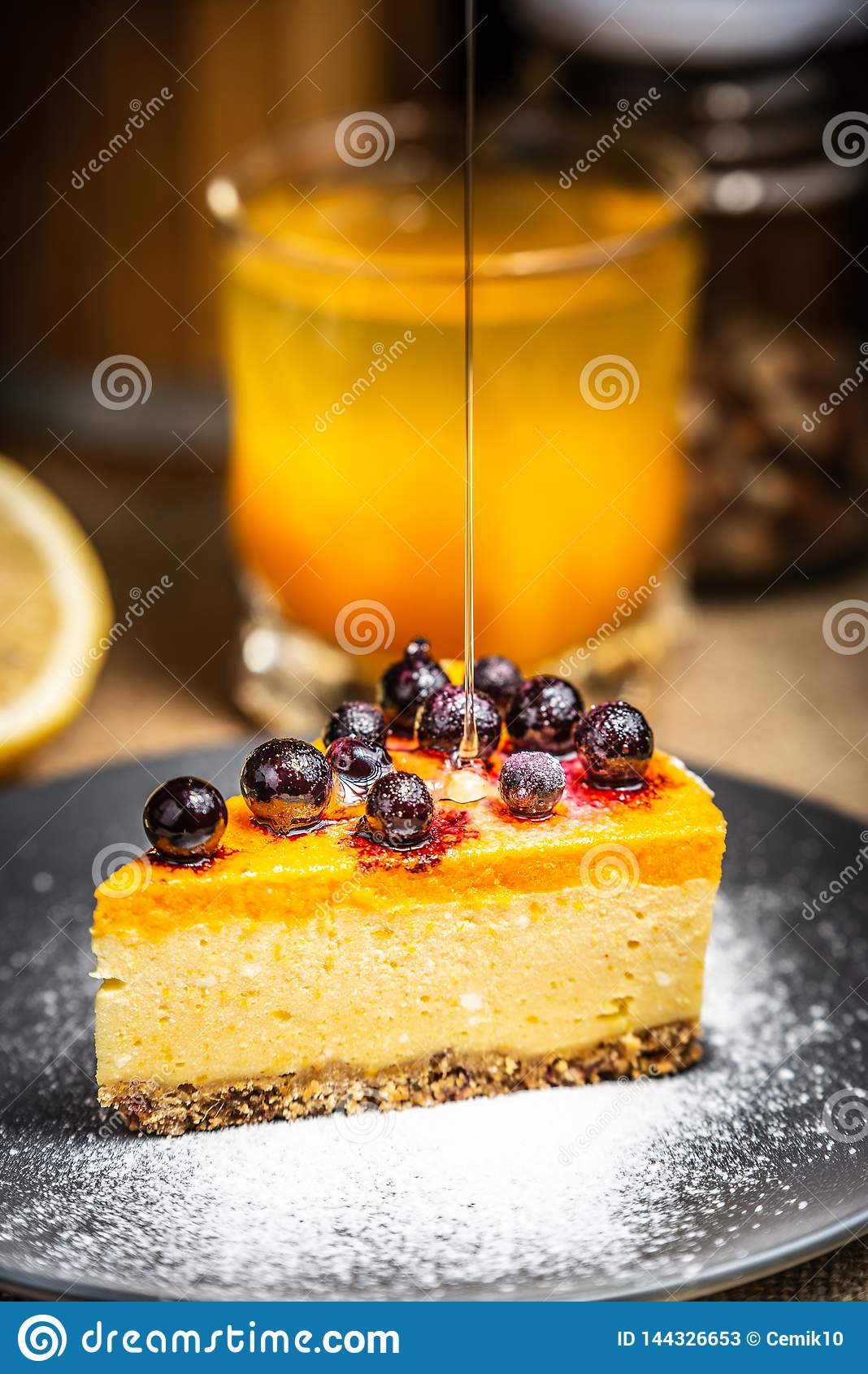 Skiva av ostkaka med b?r p? en bl? platta Tjock genombl?t honung pudrat socker