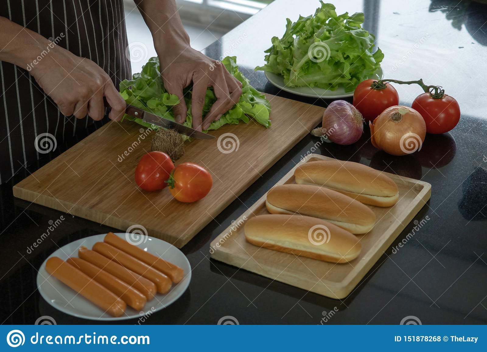 Skiva grönsaker för att förbereda ingredienser för framställning av varmkorvar