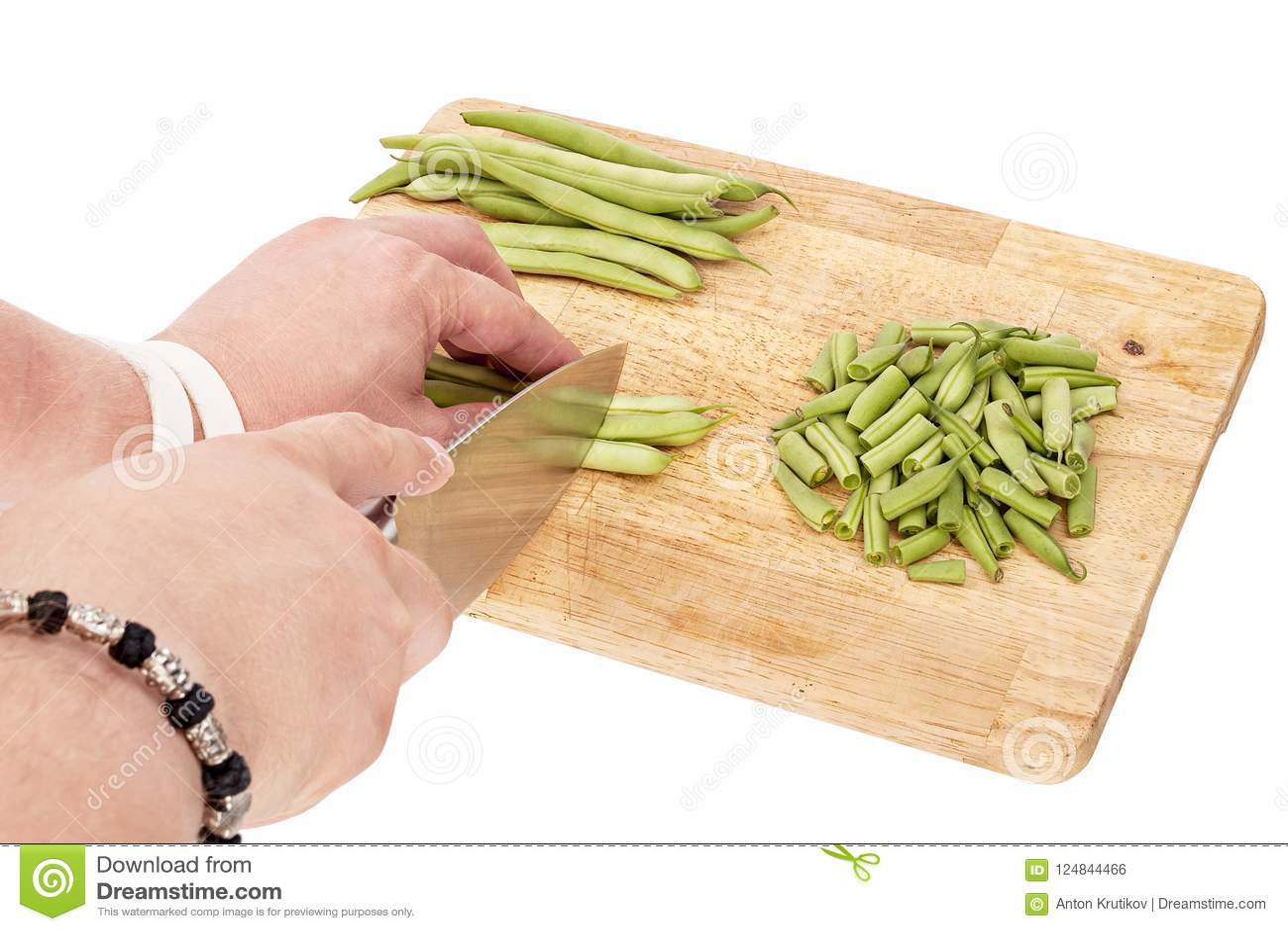 Skiva nya haricot vert på en skärbräda på en tabell