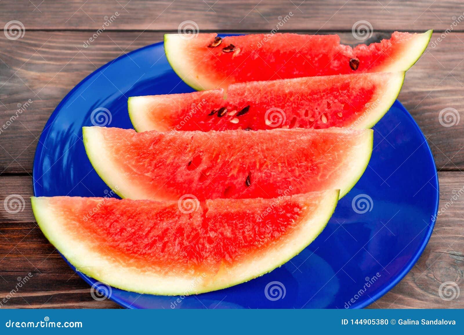 Skivad mogen r?d vattenmelon p? en bl? platta p? en tr?tabell