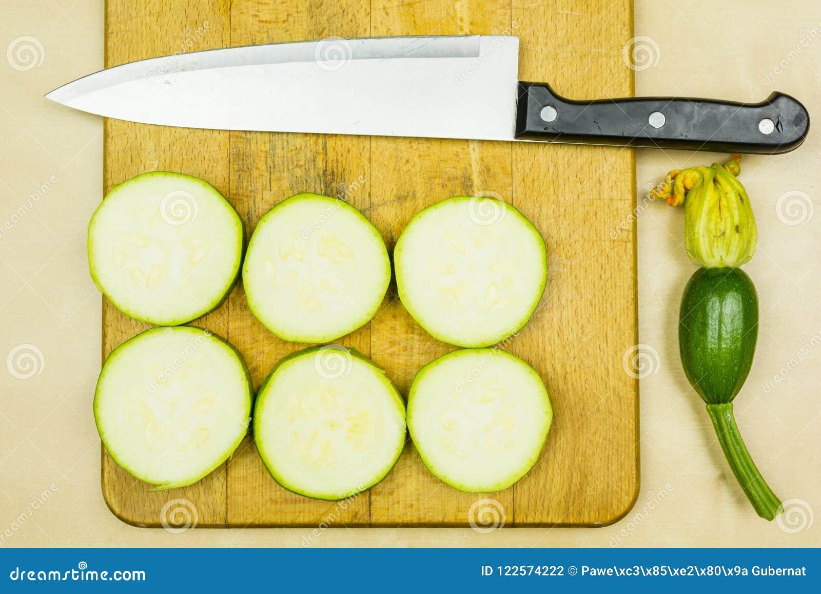 Skivad ung ny zucchini och kökkniv på skärbräda