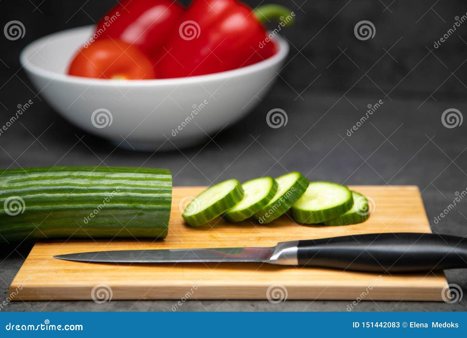 Skivade den nya gurkan på en skärbräda med en kniv och en keramisk platta av grönsaker
