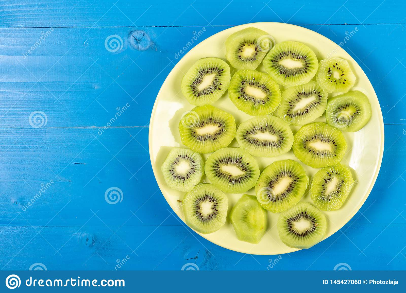 Skivade Kiwi Fruit On The Plate med bl? tabellbakgrund