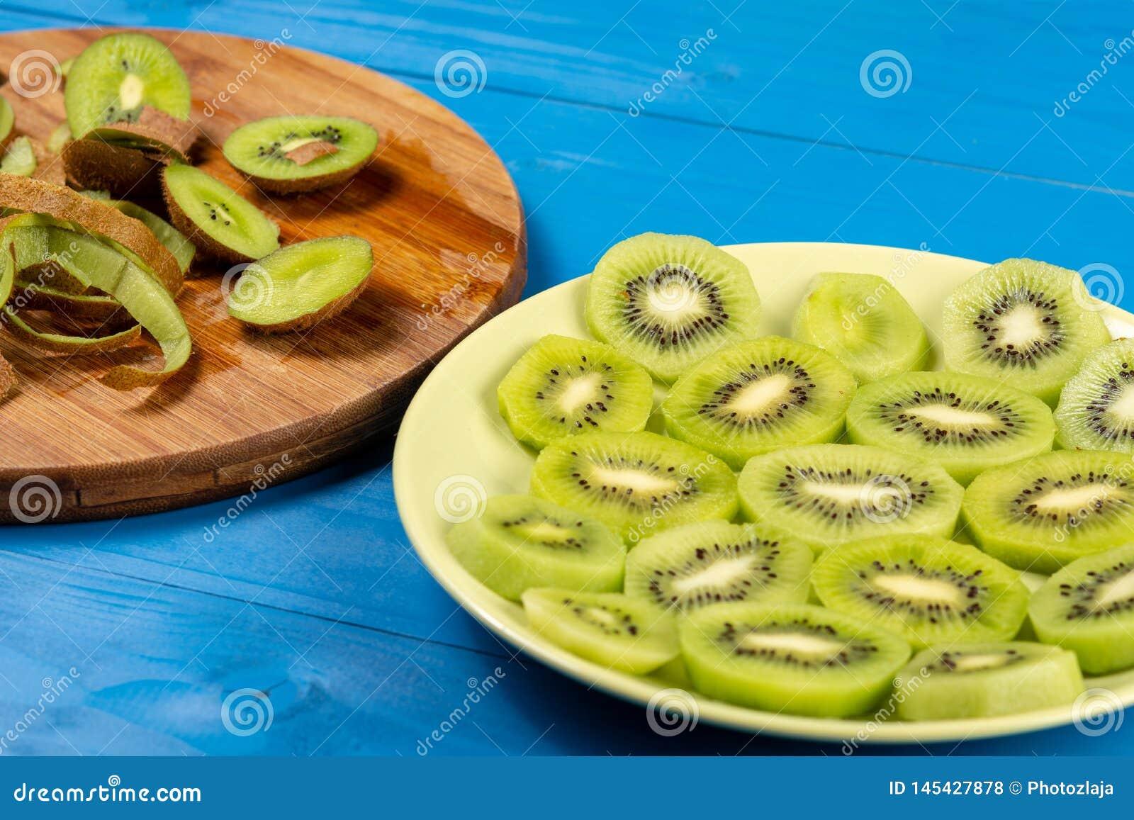 Skivade Kiwi Fruit On The Plate och träskärbräda