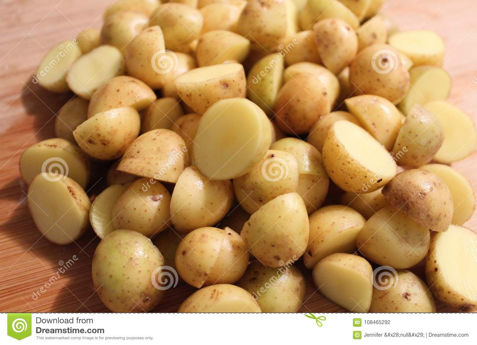 Skivade vita potatisar klippte i halva på skärbräda