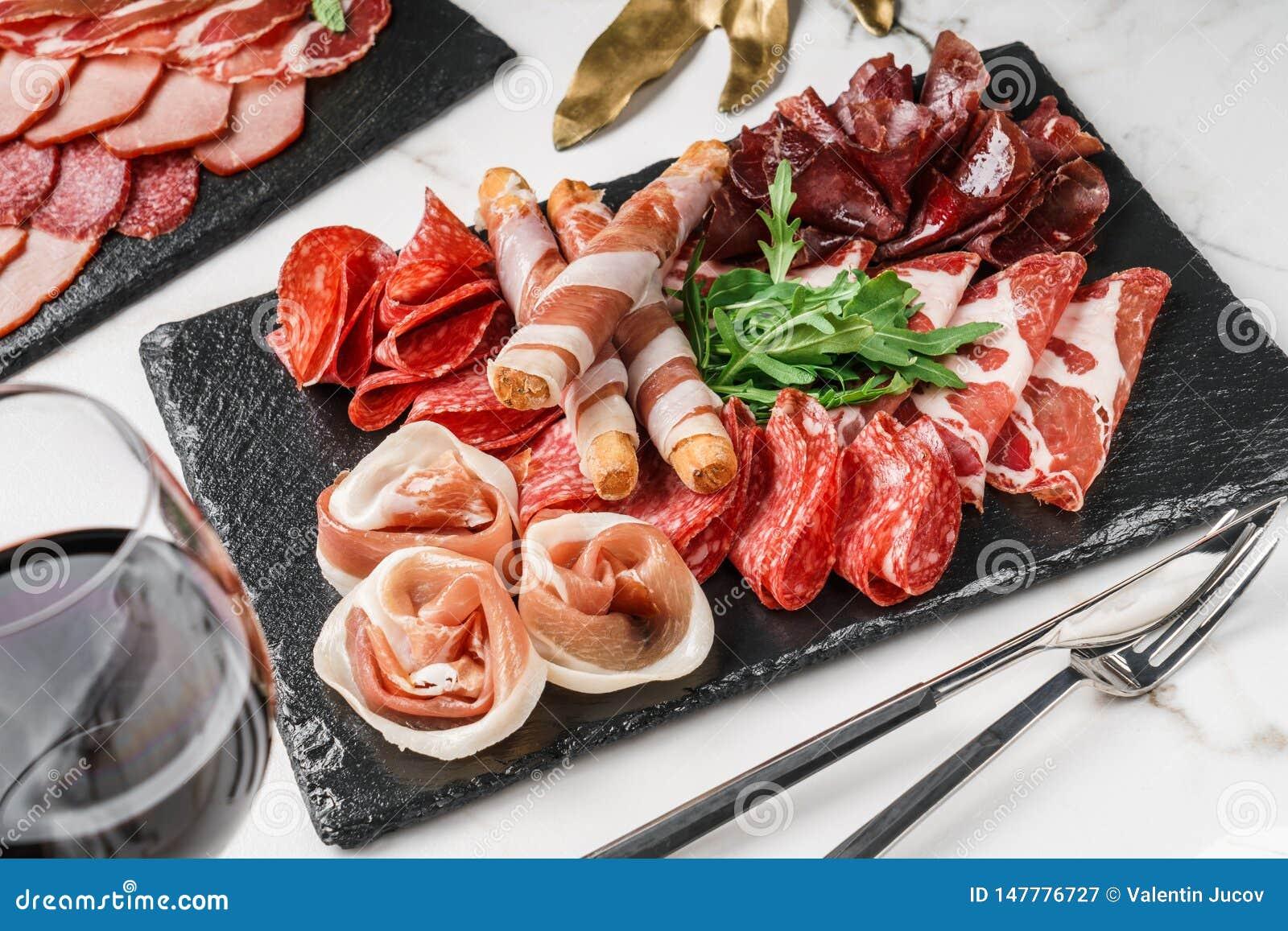Skivar kallt kött för Antipastouppläggningsfatet med grissinibrödpinnar, prosciutto, skinka, knyckigt för nötkött, salami kritise