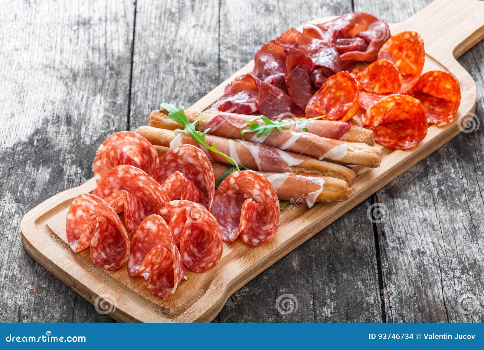 Skivar plattan för kallt kött för Antipastouppläggningsfatet med grissinibrödpinnar, prosciutto, skinka, knyckigt för nötkött, sa