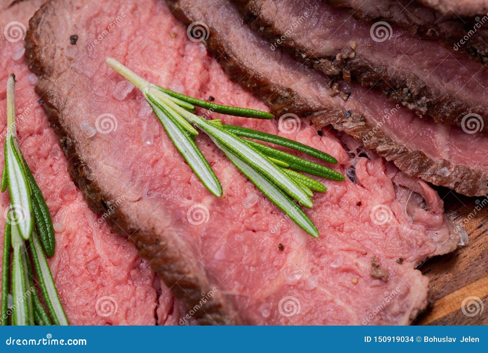 Skivat nötkött för stek för gräsFed saftigt havre som garneras med Rosemary Fresh Herb på naturlig träskärbräda