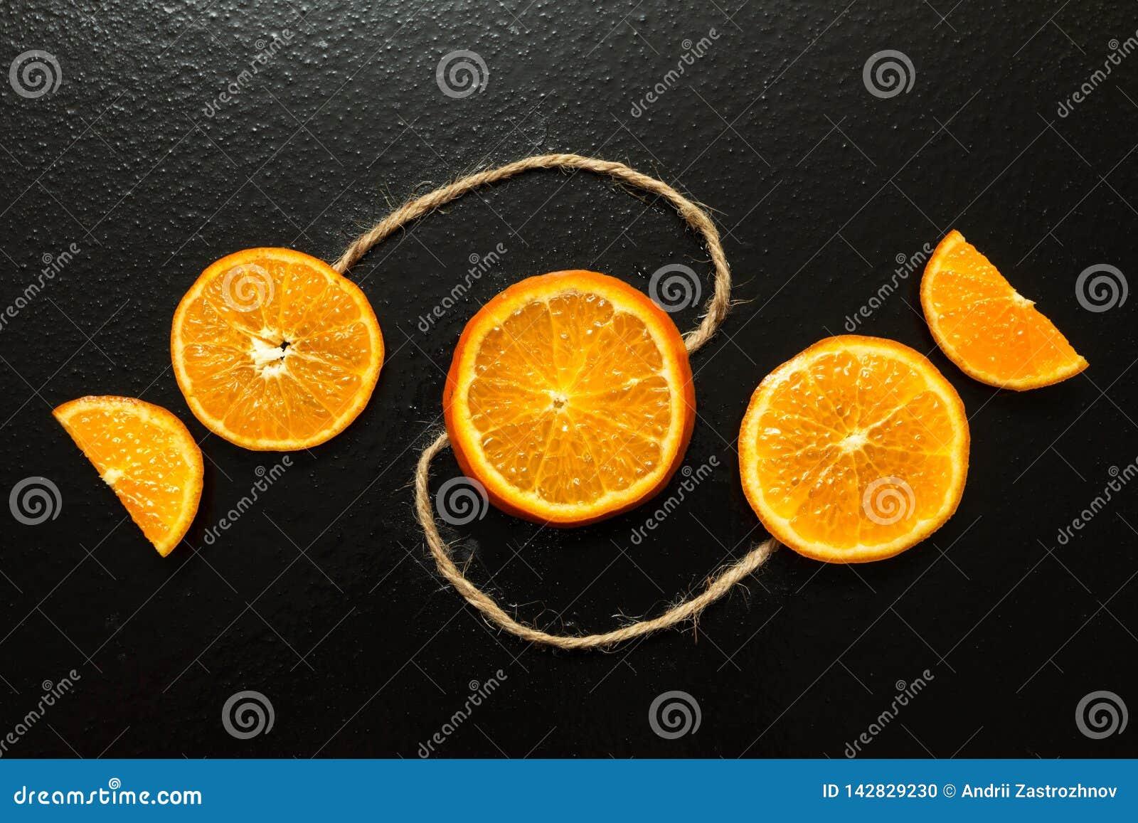 Skivor av apelsiner på en svart bakgrund