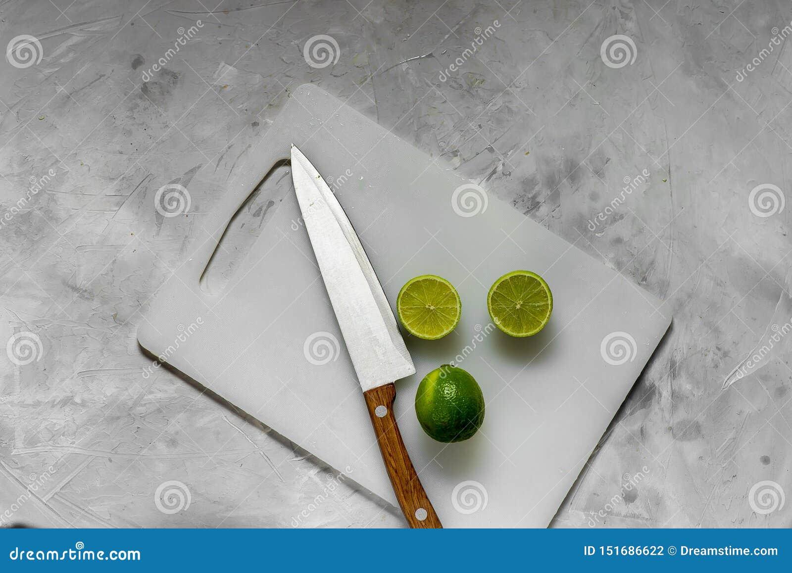 Skivor av ny grön limefrukt på kökljusbrädet