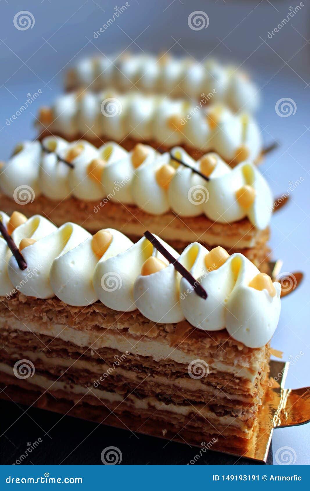 Skivor för smördegNapoleon kaka med vit toppning och citrus ostmassa på ljus bakgrund