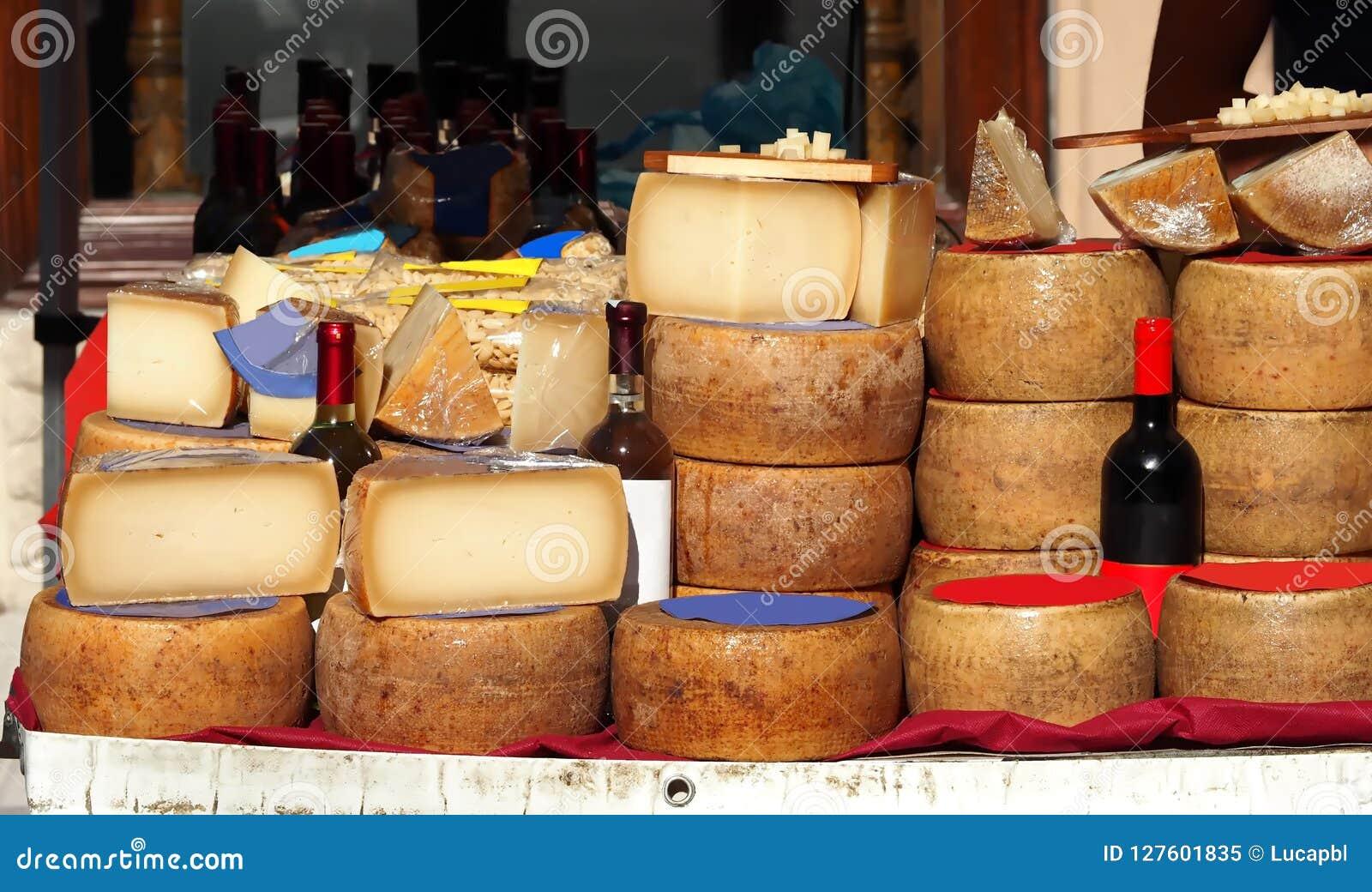 Skivor och hjul av Pecorino ost samman med flaskor av Cannonau, vitt vin, pasta och annan Sardinian typisk disk