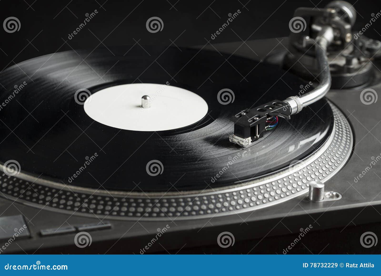 Skivtallrik som spelar upp vinyl som är nära med visaren på rekordet