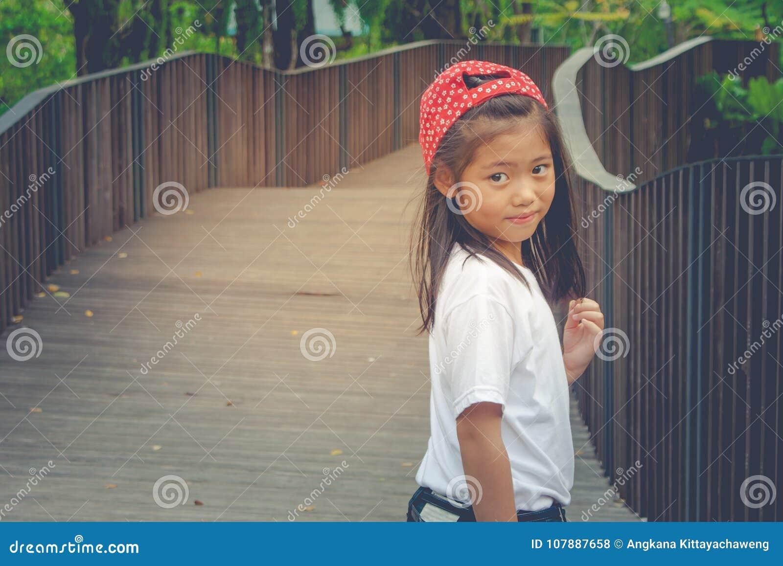 Skjuta det asiatiska gulliga liten flickaanseendet på träwalway och känslig lycka