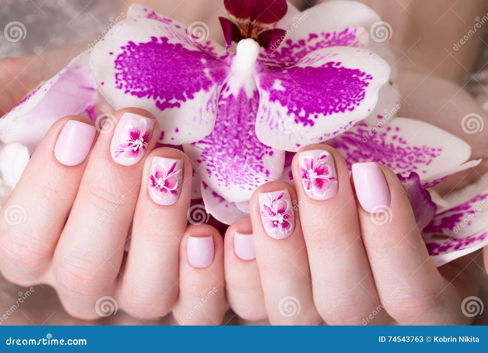 Skjuten härlig manikyr med blommor på kvinnliga fingrar Spikar design Närbild