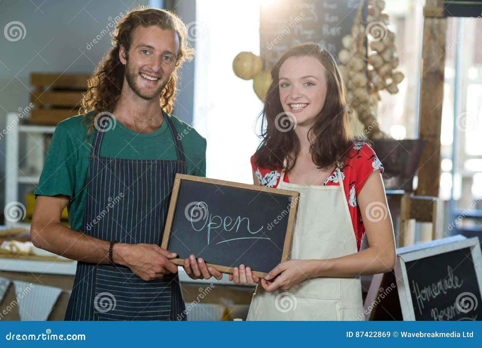 Sklepowi asystenci trzyma otwartą znak deskę