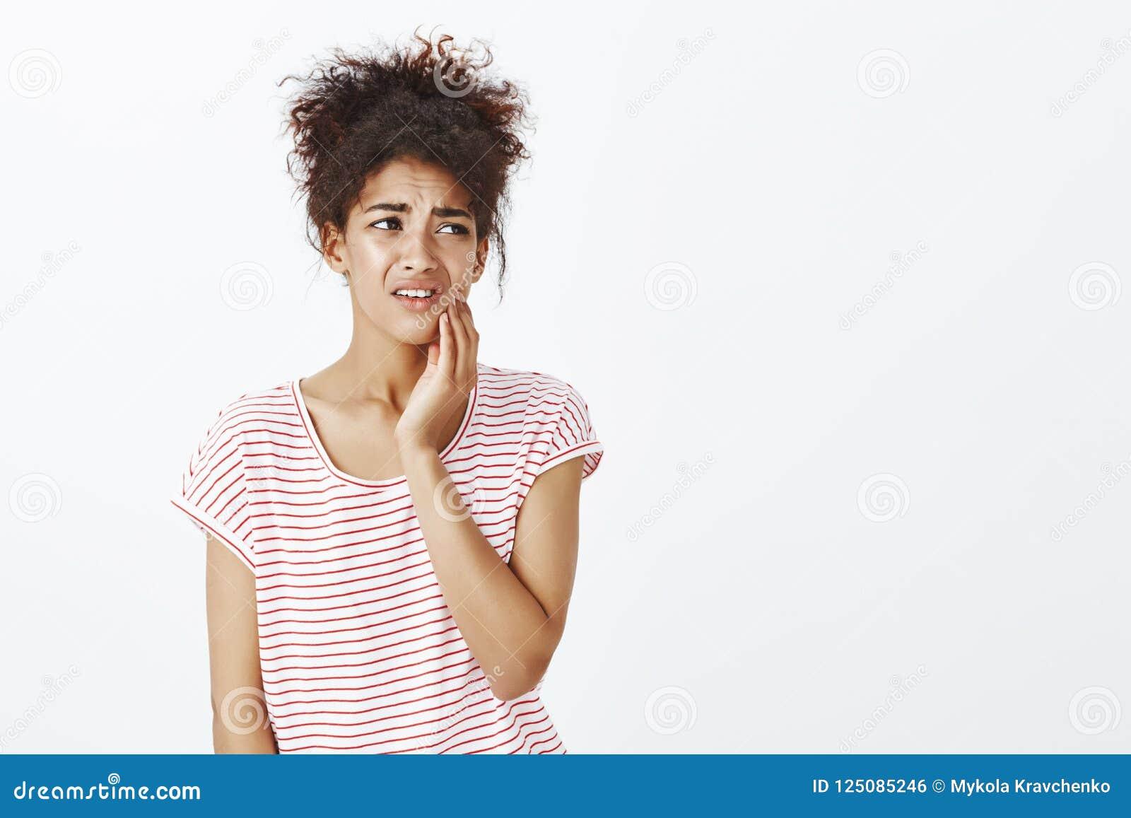 Skołatana wzburzona śliczna dziewczyna w pasiastej koszulce marszczy brwi i grimacing od bolesnego uczucia, mienie ręka na policz