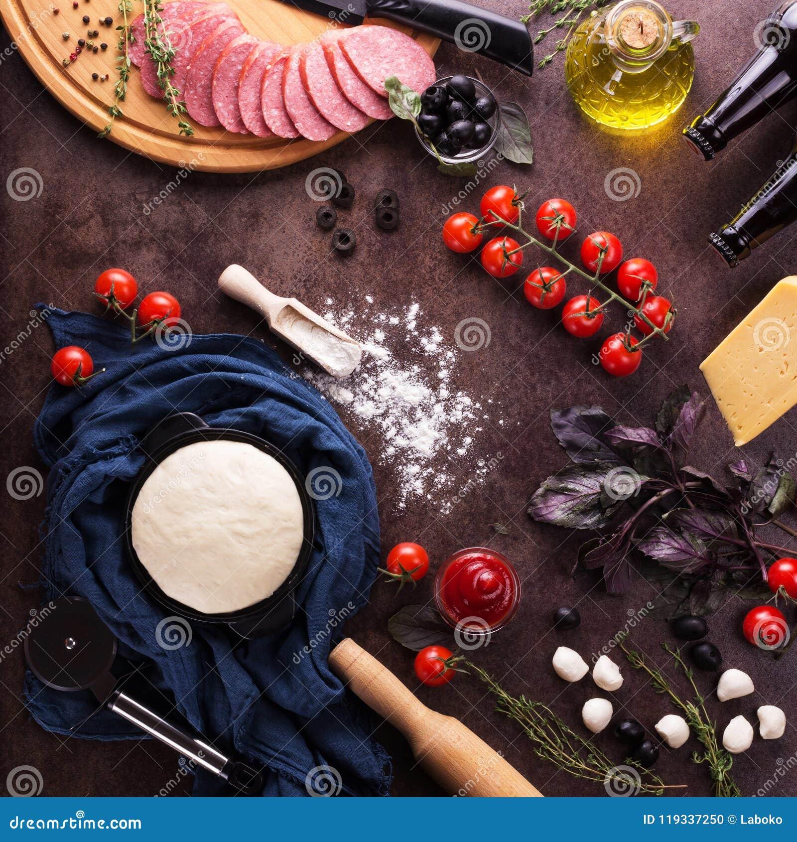 Skończony ciasto i set produkty dla kulinarnej pizzy na pracy powierzchni