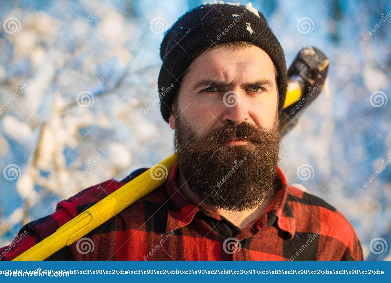 Skogsarbetare i träna med en yxa Brutal skäggig man med skägget och mustasch på vinterdag, stilig snöig skog