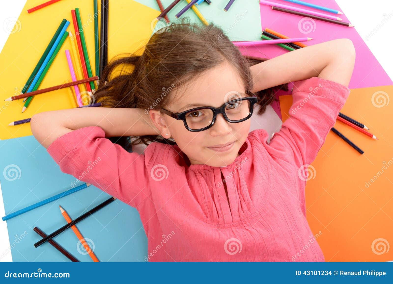 Skolaflickan som ligger på golvet med färg, ritar