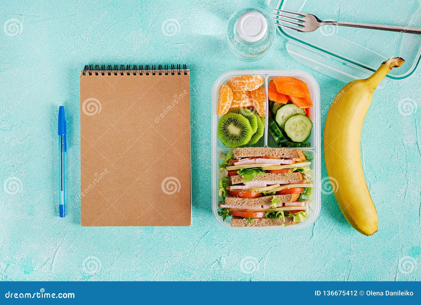 Skolalunchask med smörgåsen, grönsaker, vatten och frukter på tabellen