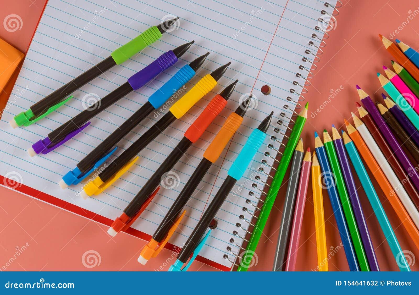 Skolatillförsel med anteckningsböcker och färgblyertspennor