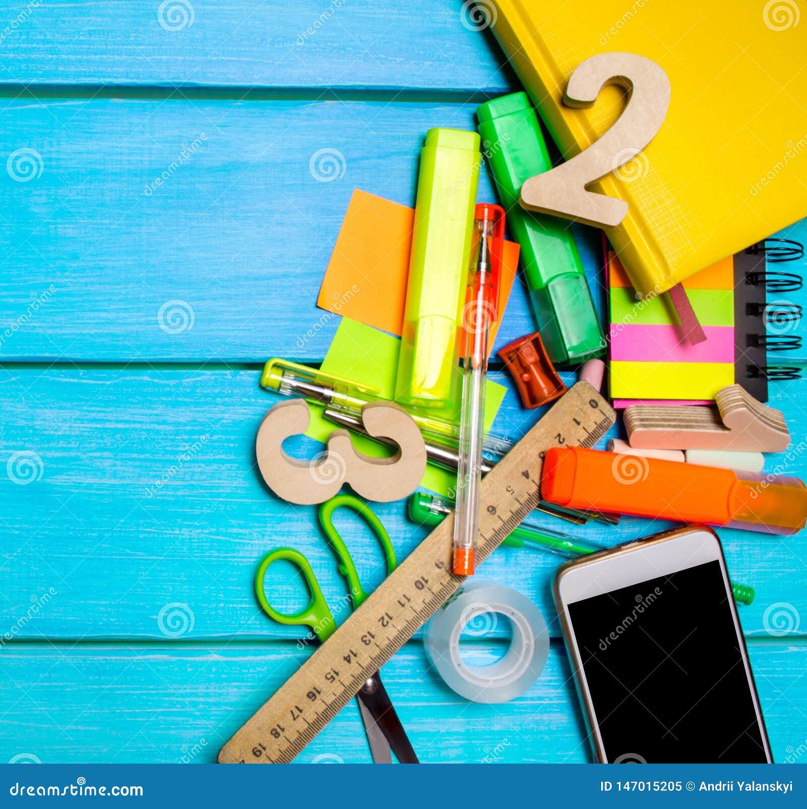 Skolatillf?rsel i skolaskrivbordet, brevpapper, skolabegrepp, bl? bakgrund, id?rikt kaos, utrymme f?r text, mark?rer, pennor,