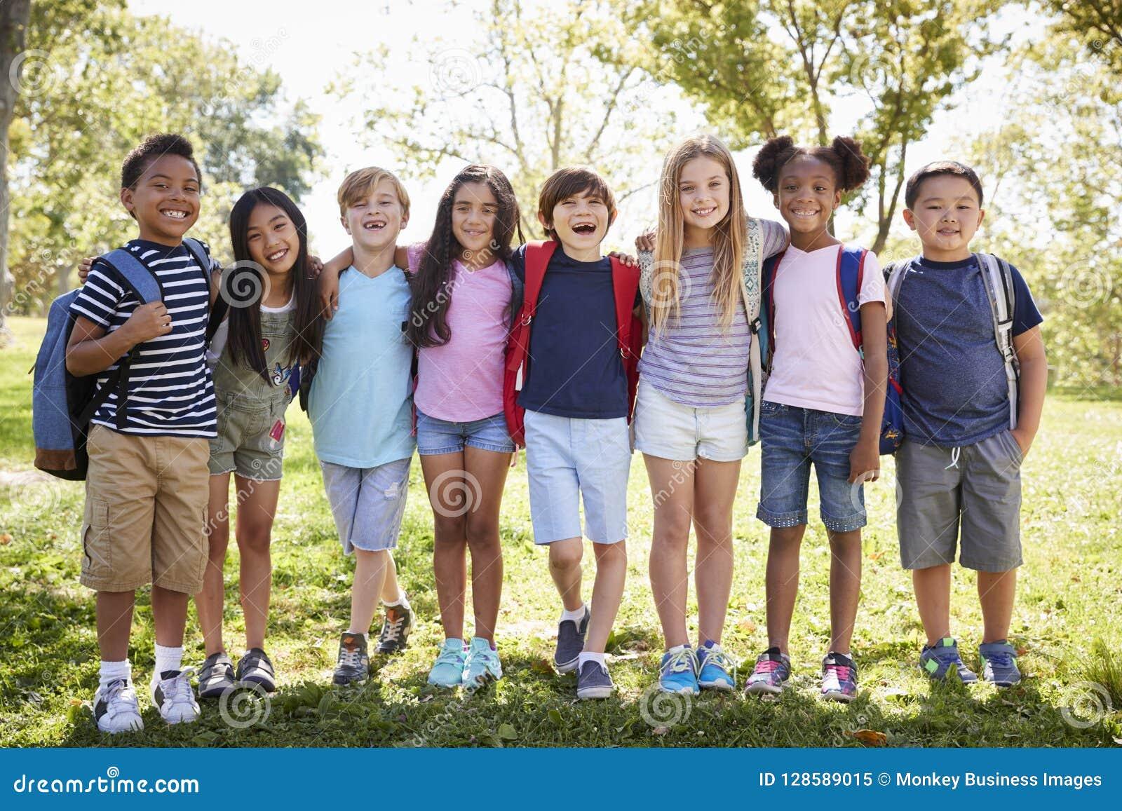 Skolaungar står omfamna i rad utomhus, den fulla längden