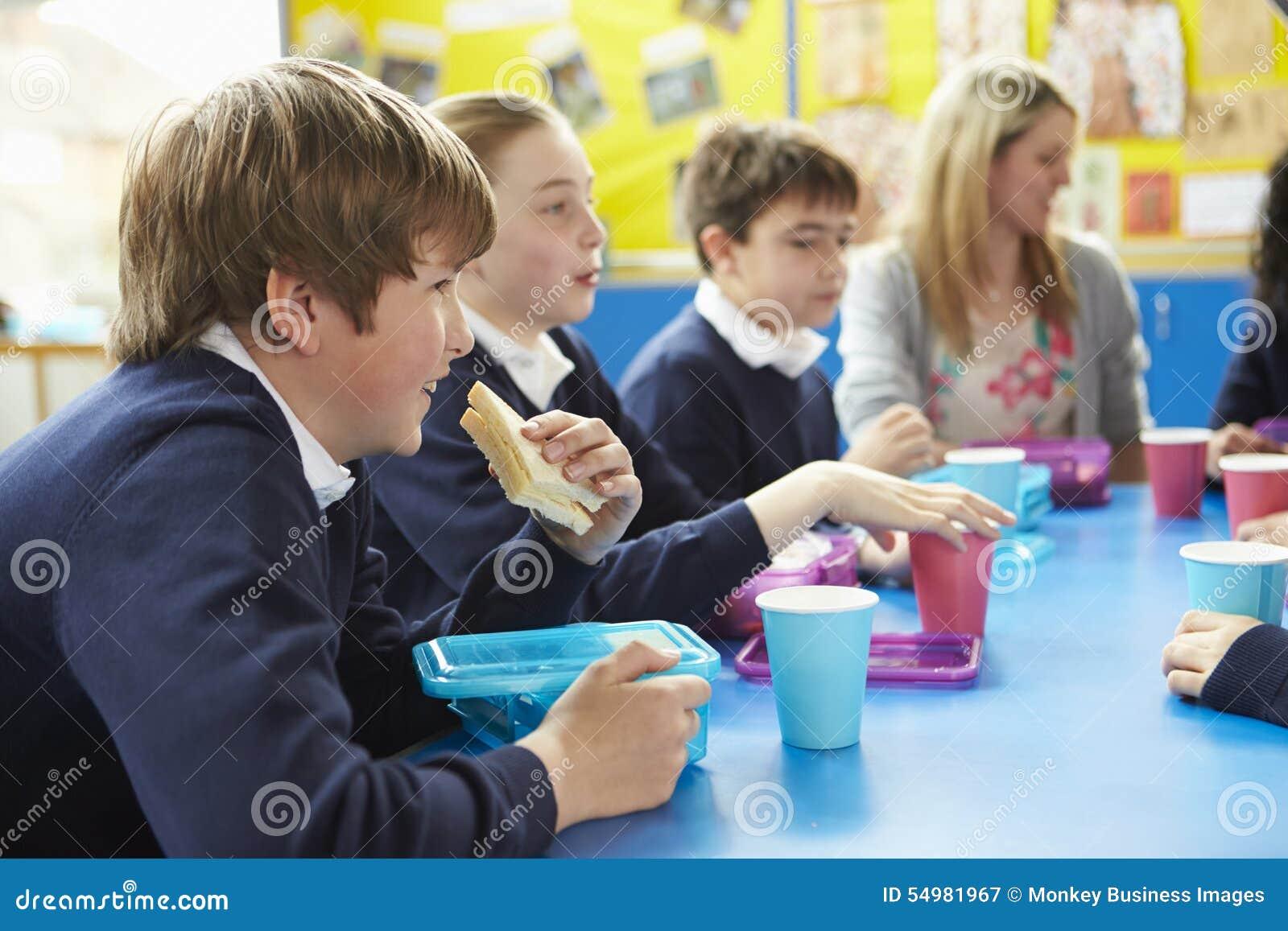 Skolbarn med läraren Sitting At Table som äter lunch