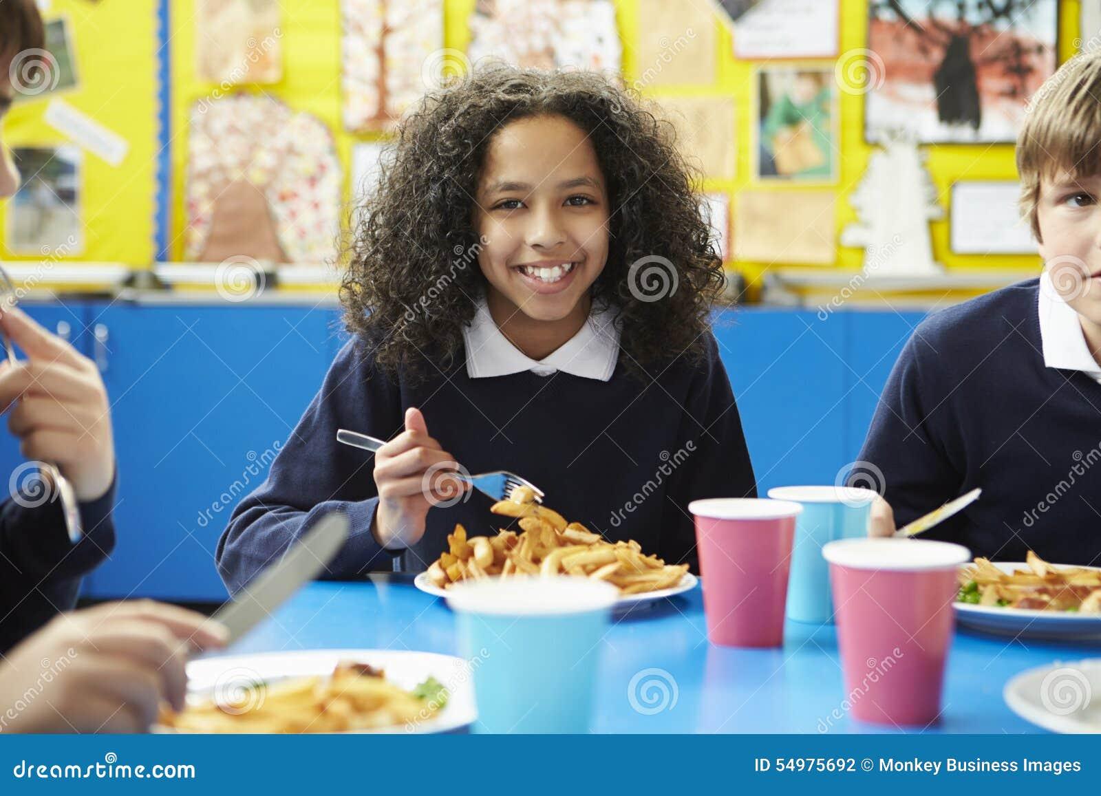 Skolbarn som sitter på tabellen som äter lagad mat lunch