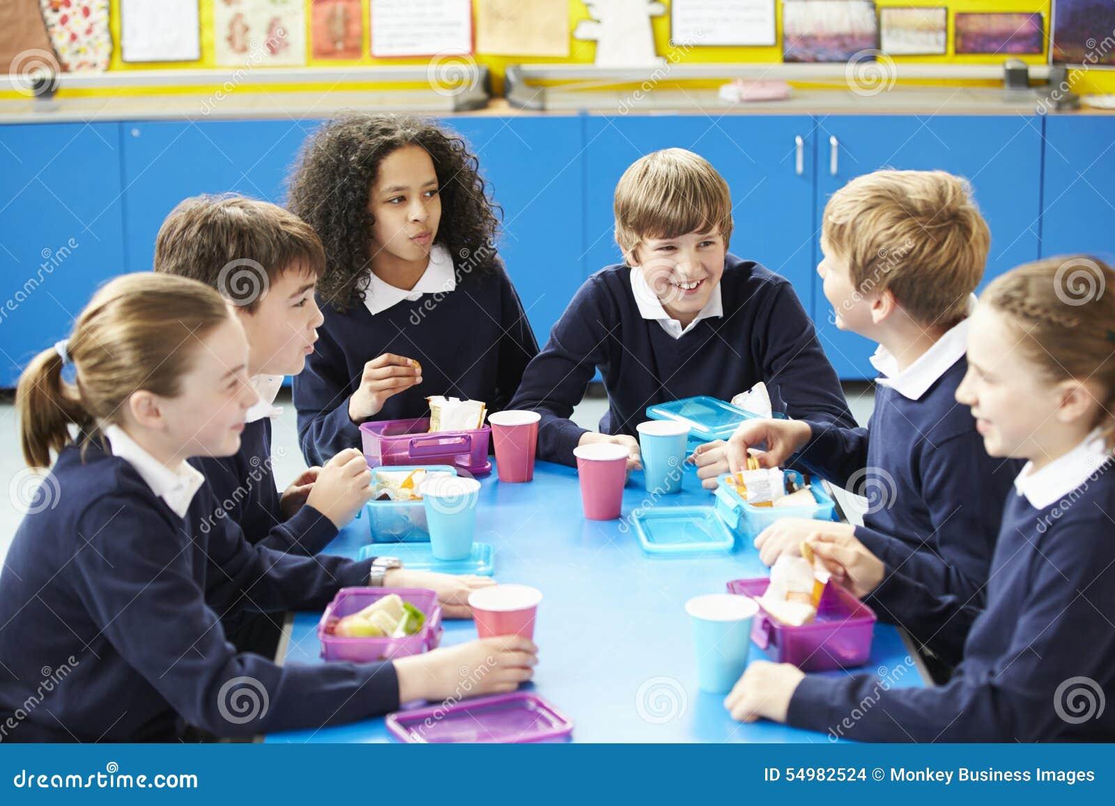 Skolbarn som sitter på tabellen som äter matsäck