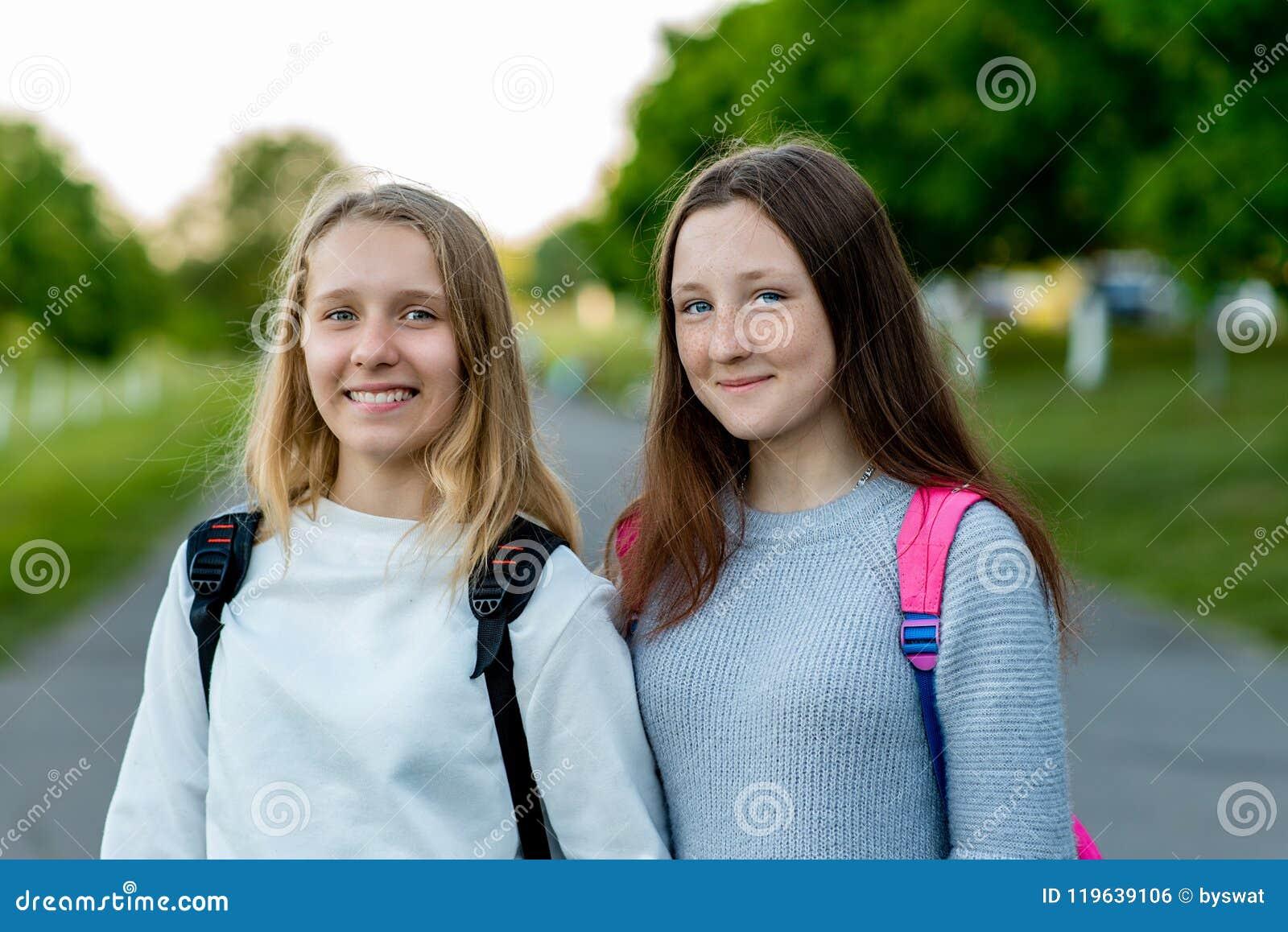 Skolflicka för två flickavänner Flickor vilar efter skola Sommar i natur Bak ryggsäckar Det bästa begreppet av kamratskap