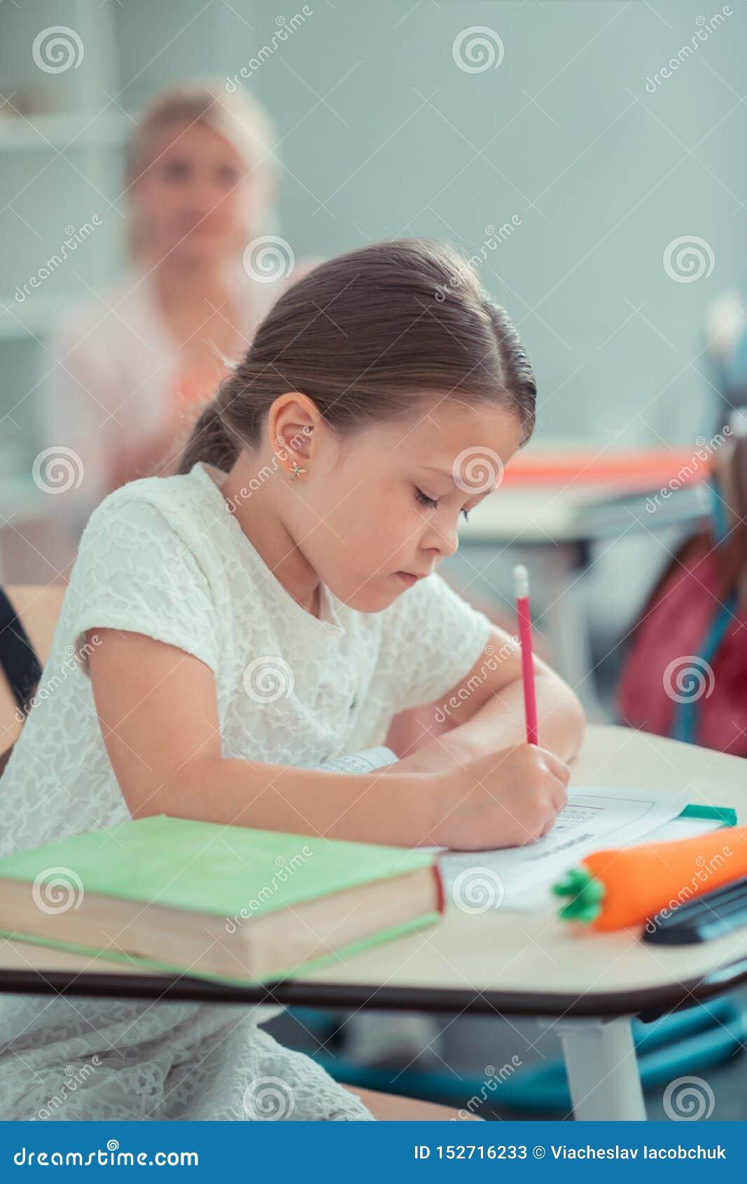 Skolflicka som hårt arbetar på hennes matematikprov