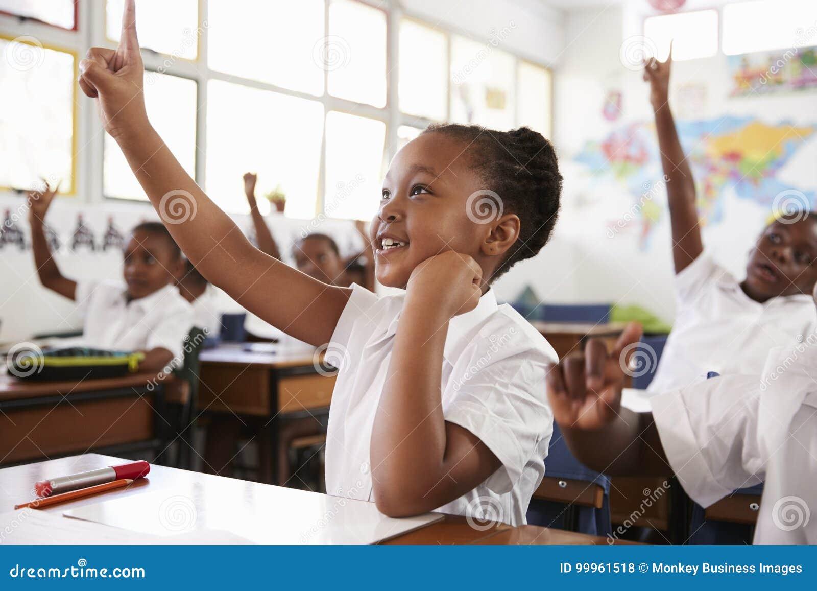Skolflicka som lyfter handen under en kurs på grundskolan