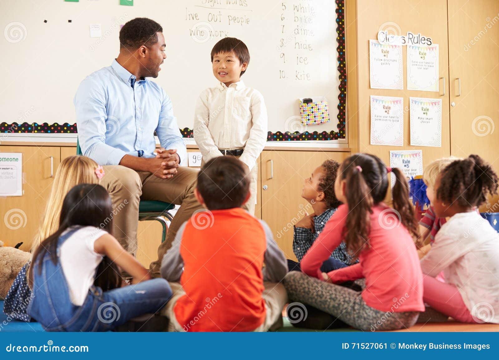 Skolpojke på framdelen av elementär grupp med läraren