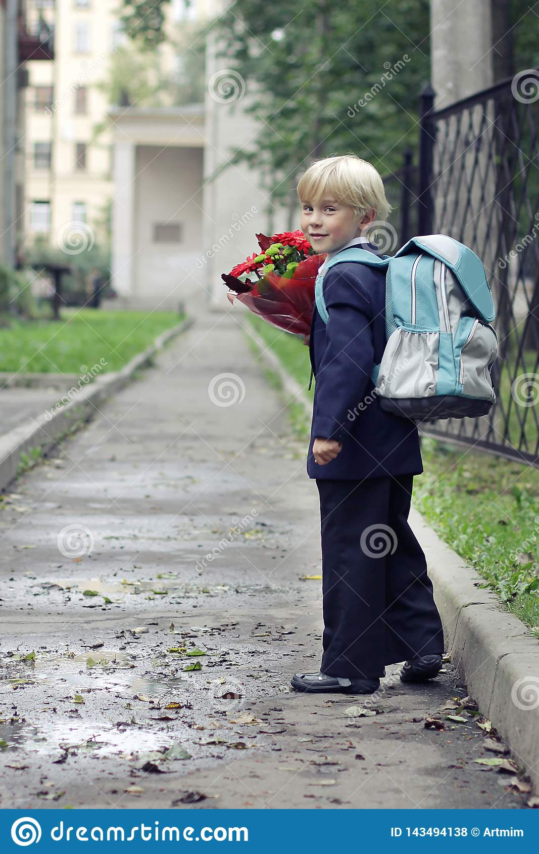 Skolpojke på hans väg till skolan Pojke som går till första klass i hans skola på banan Barn och utbildning i staden