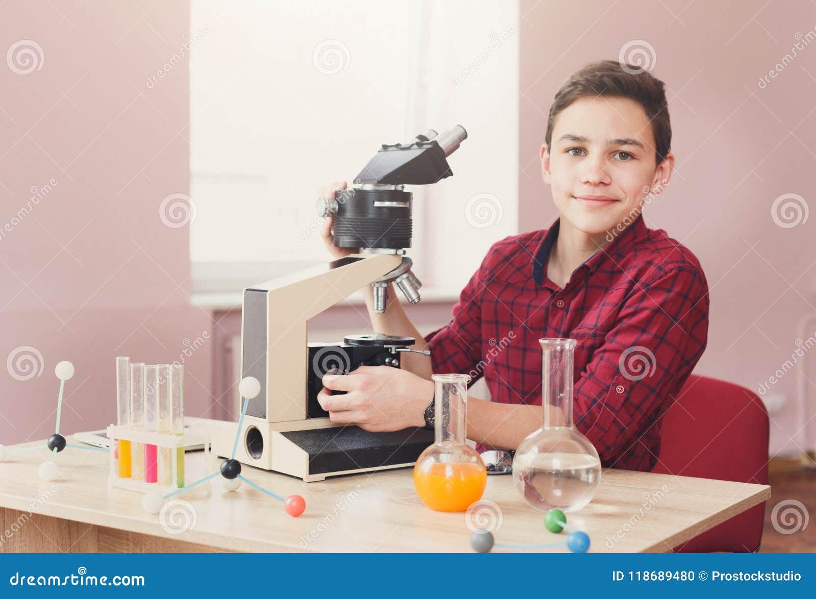 Skolpojke som ser i mikroskop på kurs