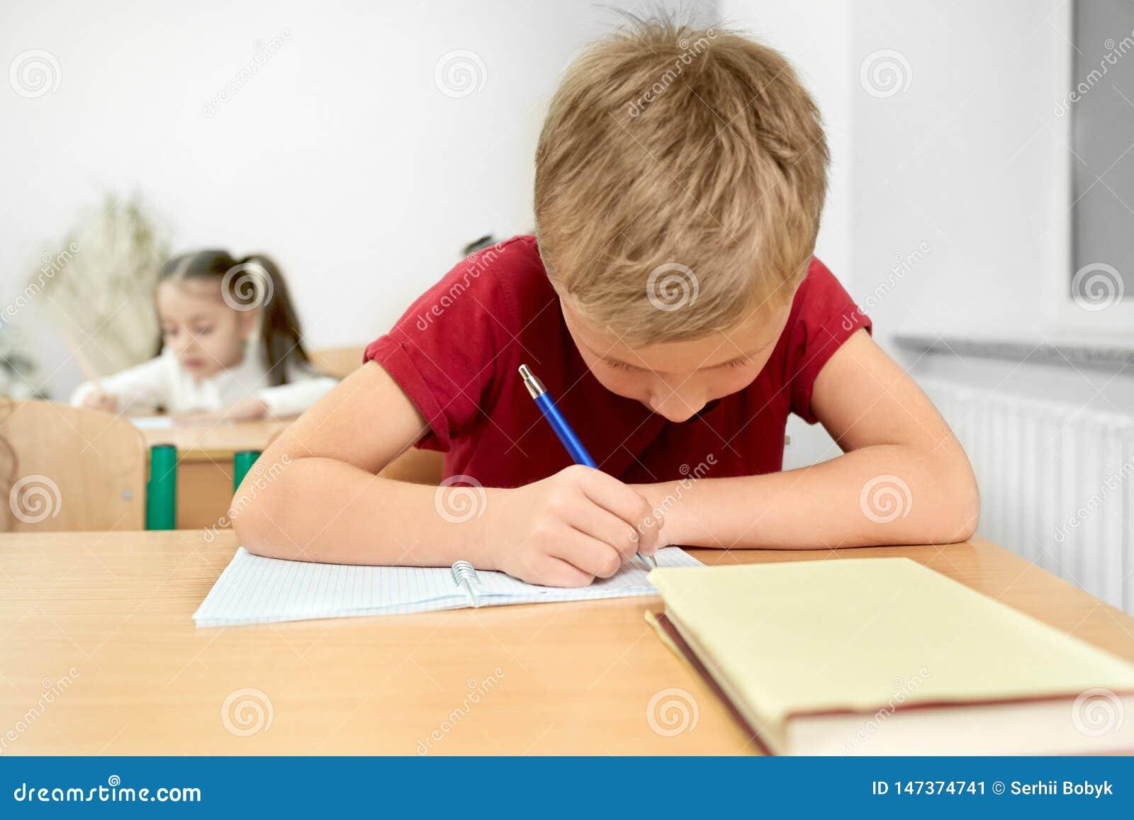 Skolpojke som sitter på skrivbordet som skriver med pennan i förskriftsbok