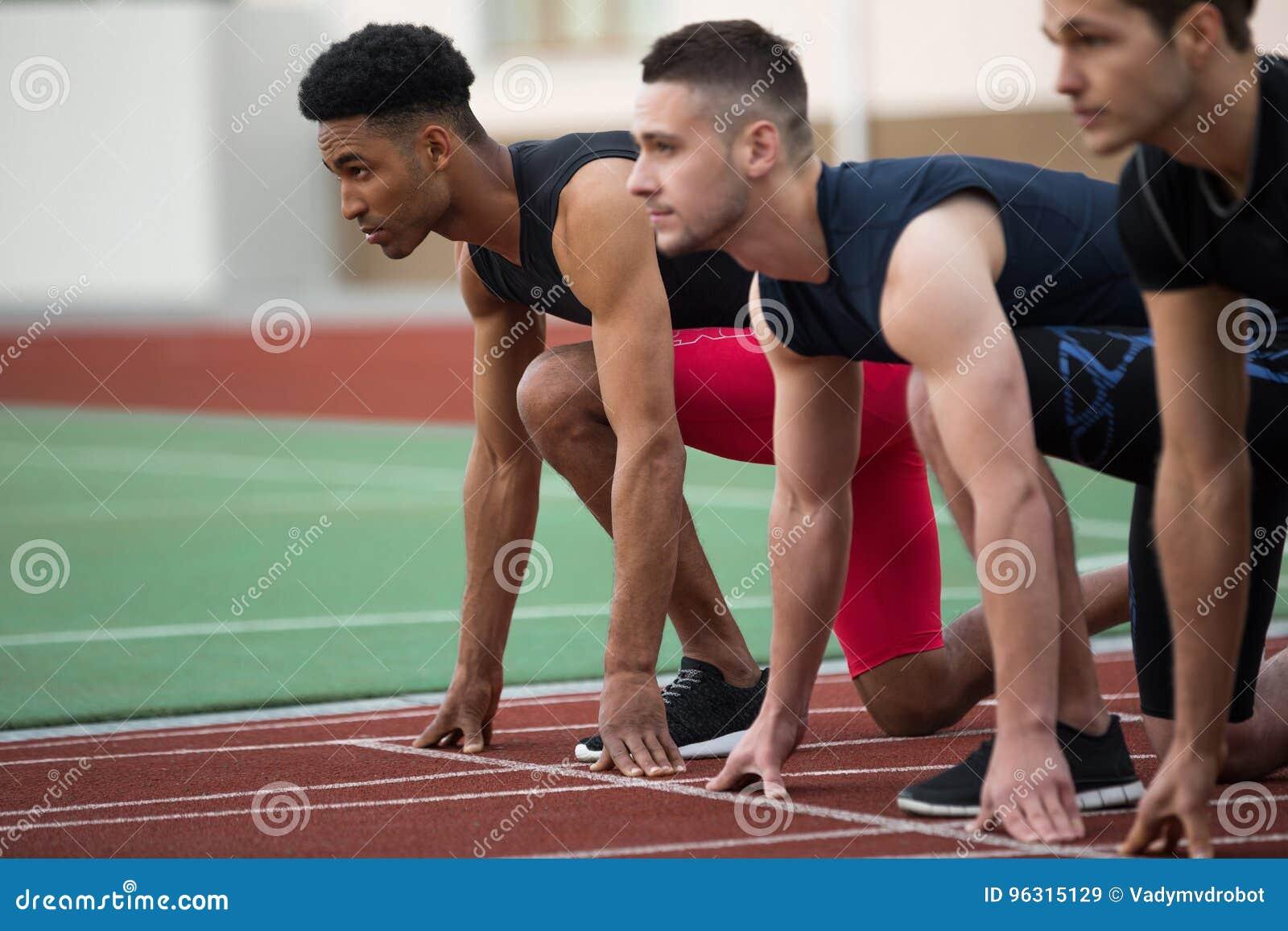 Skoncentrowana wieloetniczna atlety grupa przygotowywająca bieg