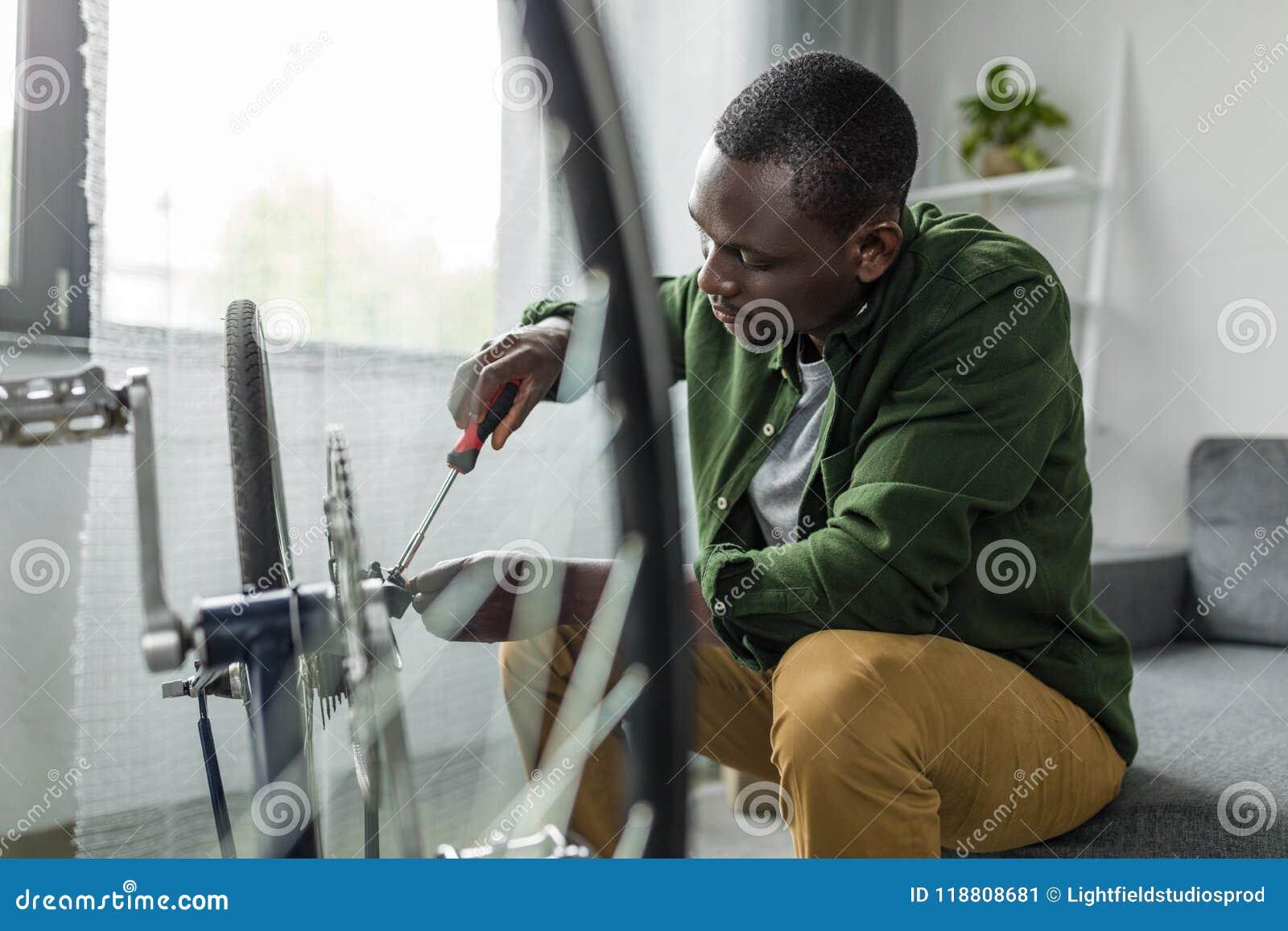 Skoncentrowany afro mężczyzna naprawiania bicykl z śrubokrętem