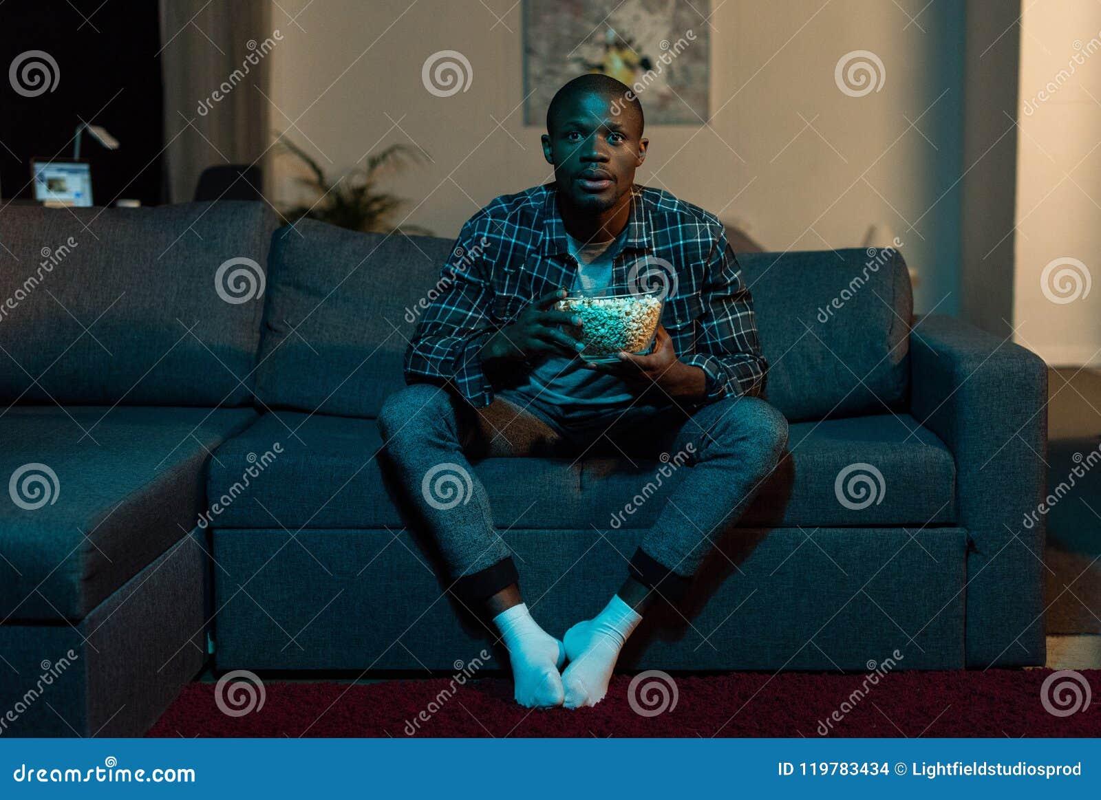 Skoncentrowany amerykanina afrykańskiego pochodzenia mężczyzna ogląda tv z popkornem w rękach