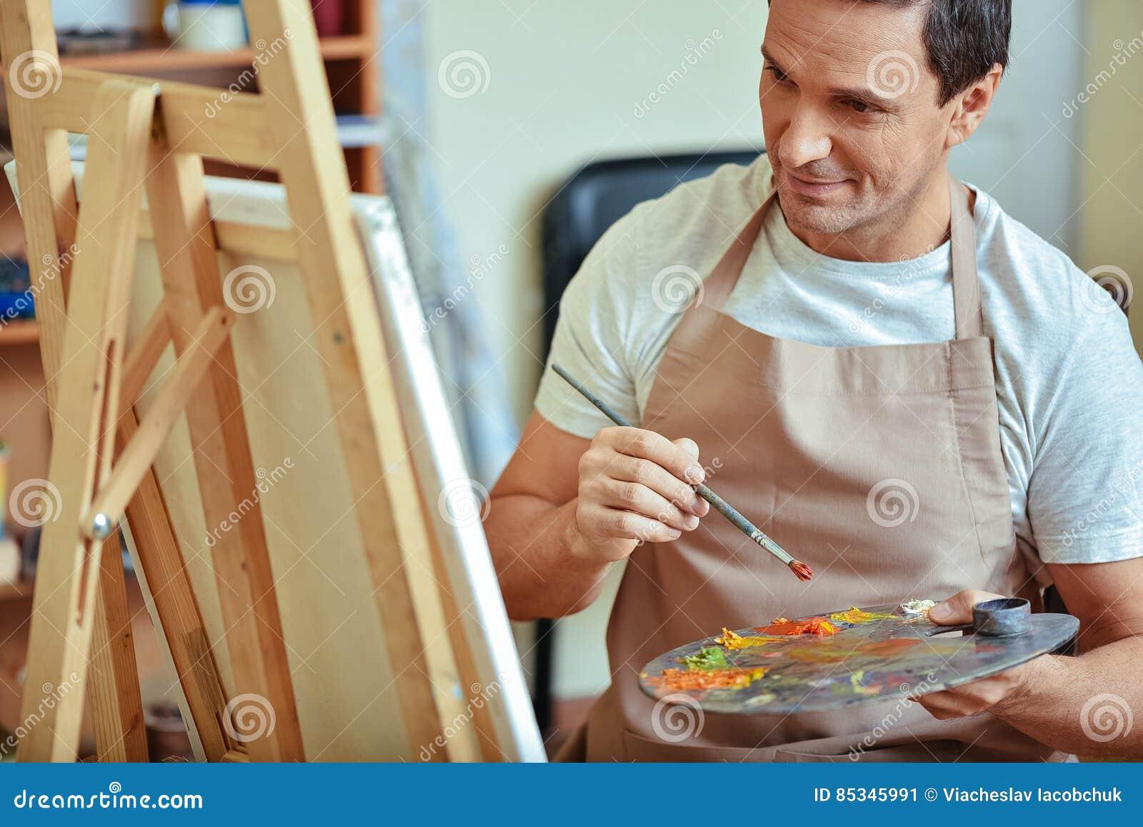 Skoncentrowany artysta trzyma paletę i muśnięcie