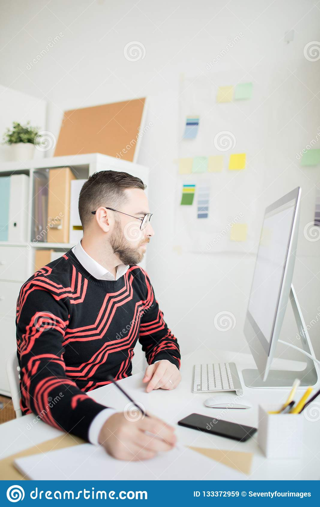 Skoncentrowany biznesmen robi notatce podczas gdy trzymający online analys
