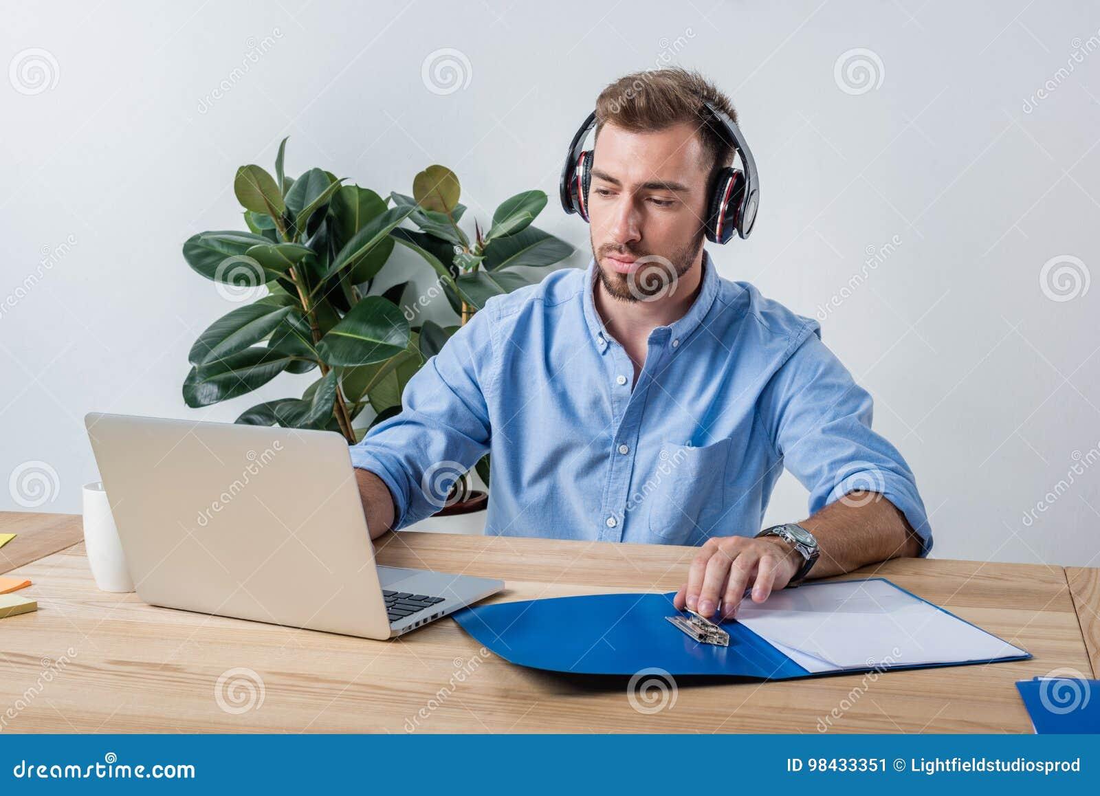 Skoncentrowany biznesmen w hełmofonach pracuje z dokumentami i laptopem w biurze