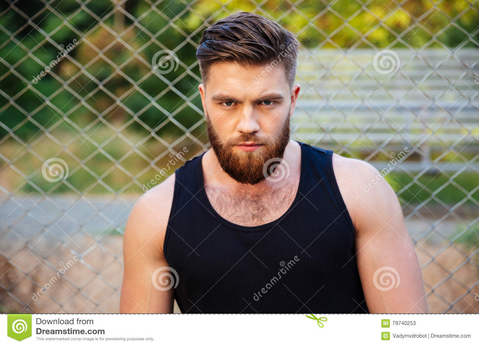 Skoncentrowany brodaty mężczyzna patrzeje kamerę w tshirt