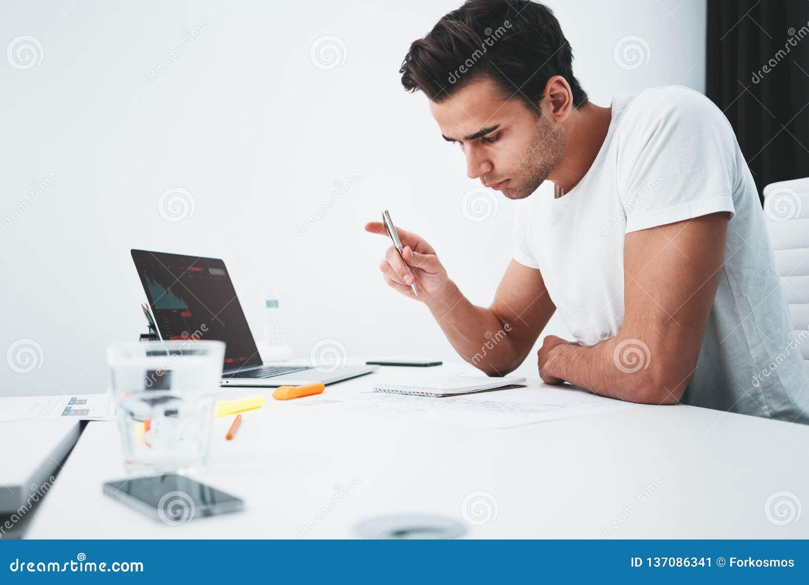 Skoncentrowany budynku projektant pracuje z rysunku competer i planem podczas gdy siedzący stołem przy pracownianym biurem