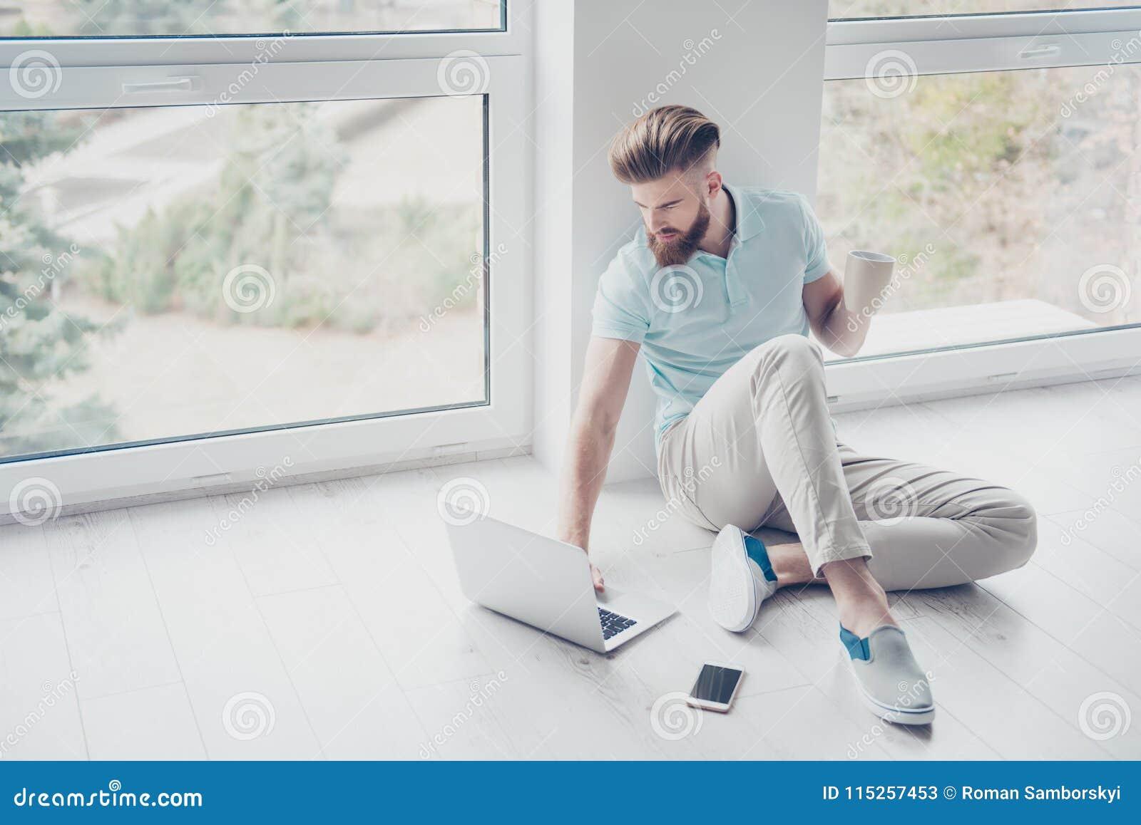 Skoncentrowany elegancki czerwony brodaty mężczyzna siedzi na podłoga przy