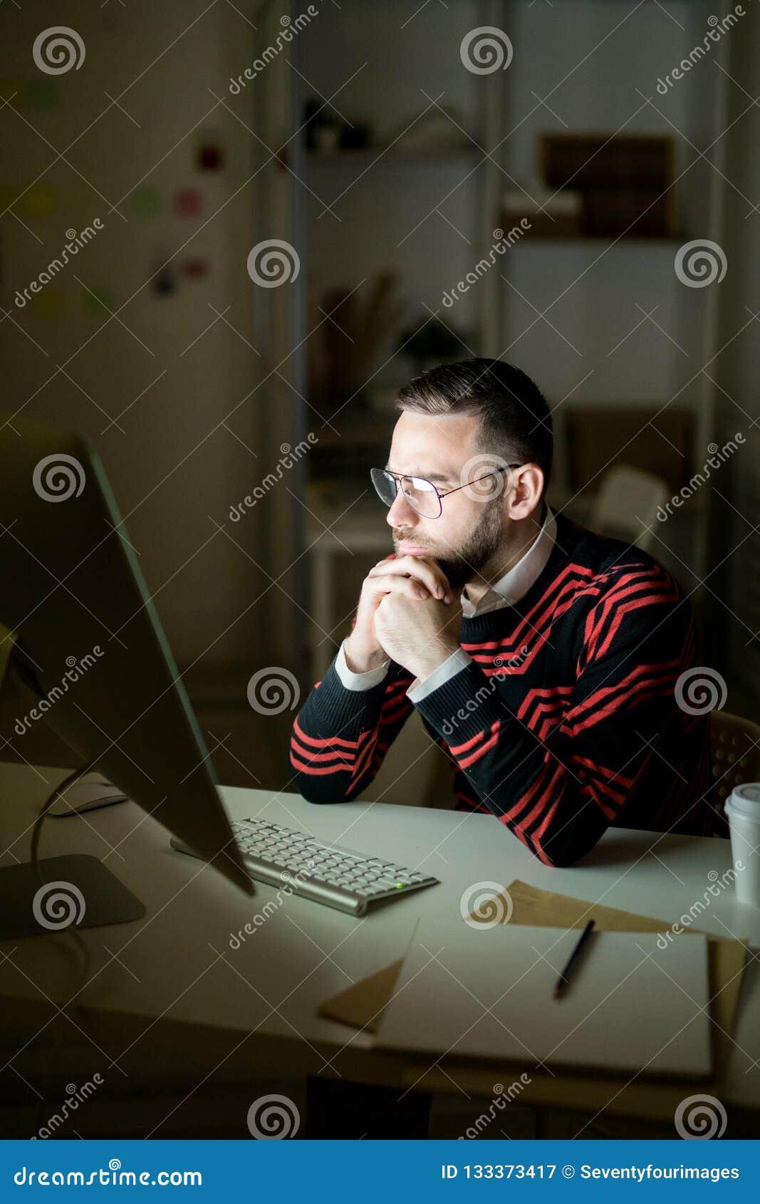 Skoncentrowany kierownik egzamininuje raport przy nocą